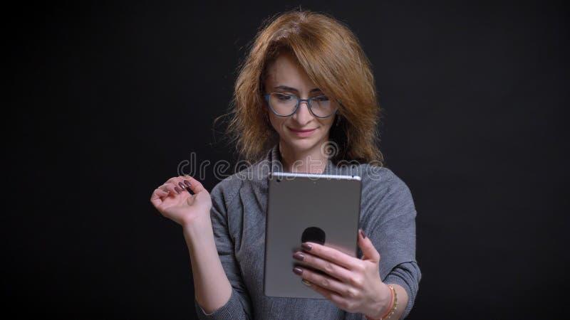 Close-upportret van roodharigewijfje op middelbare leeftijd in glazenoverseinen op de tablet voor de camera met achtergrond stock fotografie