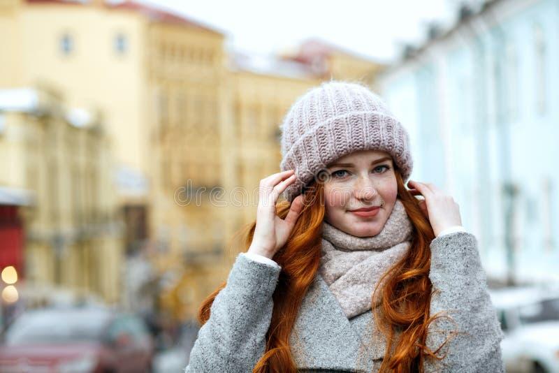 Close-upportret van schitterend rood haired meisje die gebreide oorlog dragen royalty-vrije stock afbeelding