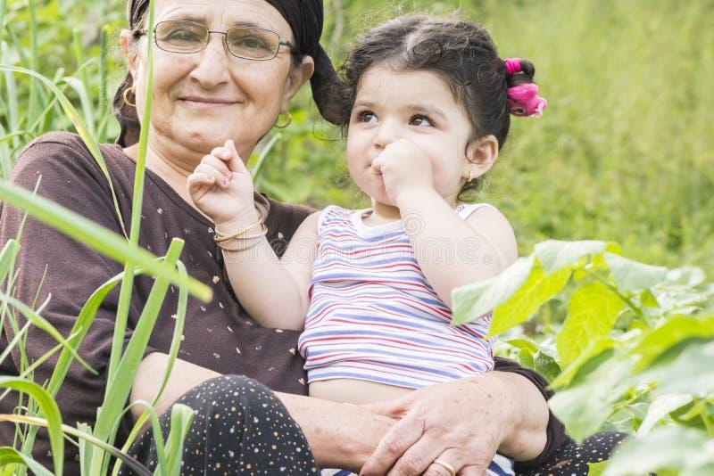 Close-upportret van Senor-Grootmoeder met haar weinig kleinkind die bij tuin samen van genieten royalty-vrije stock fotografie
