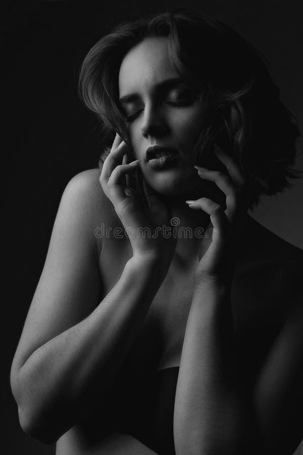 Close-upportret van sensueel donkerbruin model met krullend haar en naakte schouders Het zwart-witte stemmen royalty-vrije stock afbeelding