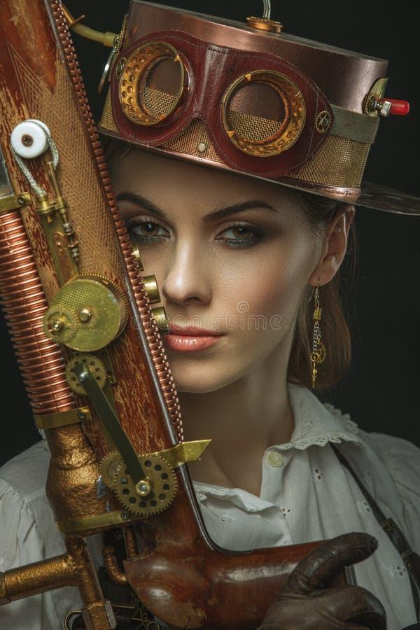 Close-upportret van steampunkmeisje met een kanon in zijn hand stock foto