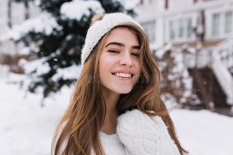 Close-upportret van tevreden blondevrouw die met oprechte glimlach de winter van ochtend genieten Mooi Europees meisje in witte h stock foto's