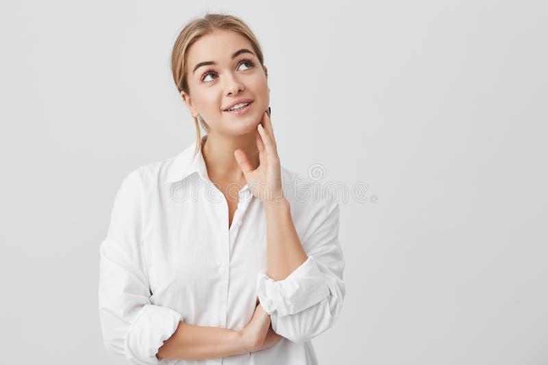 Close-upportret van tevreden vrouw met zuivere huid, donkere ogen en oprechte glimlach die het witte overhemd stellen dragen tege royalty-vrije stock fotografie