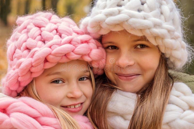 Close-upportret van twee gelukkige glimlachende meisjes in hoeden en sjaals van de ruwe met de hand gebreide Kerstmiswinter stock afbeeldingen