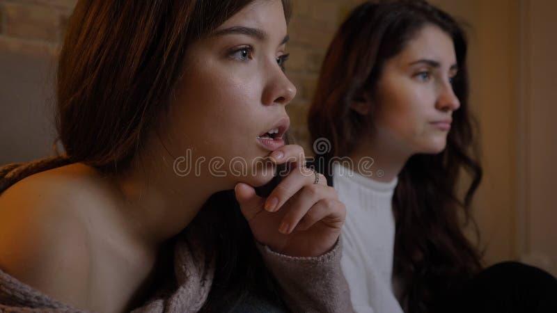 Close-upportret van twee jonge mooie vrouwen die op TV met opwinding in een comfortabele flat binnen letten stock foto