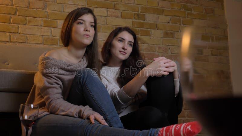 Close-upportret van twee jonge mooie vrouwen die TV-op het koelen met wijnzitting letten op de vloer in een comfortabele flat stock foto