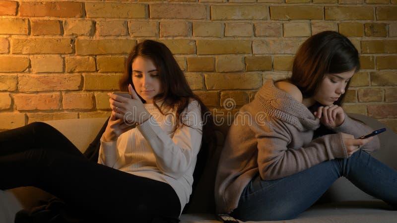 Close-upportret van twee jonge vrij Kaukasische meisjes die op de telefoons doorbladeren terwijl het rusten op de laag binnen in  stock afbeeldingen