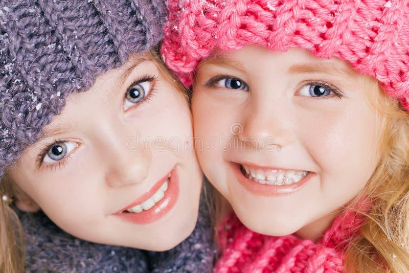 Close-upportret van twee leuke kleine zusters in de winterkleren Roze en grijze hoeden en sjaals Familie stock afbeeldingen