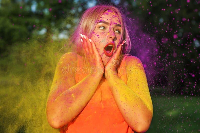 Close-upportret van verrast blondemodel die pret in een wolk van gele en purpere droge Holi-verf hebben stock foto