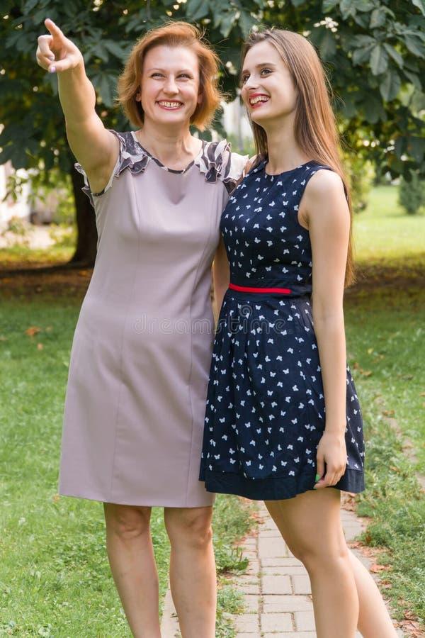 Close-upportret van volwassen dochter en moeder in openlucht Het mooie brunette en haar mamma bekijken de camera in royalty-vrije stock afbeeldingen