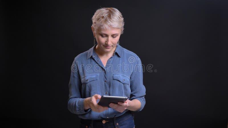 Close-upportret van volwassen vrij Kaukasisch wijfje met kort blondehaar die de tablet voor de camera gebruiken met stock foto