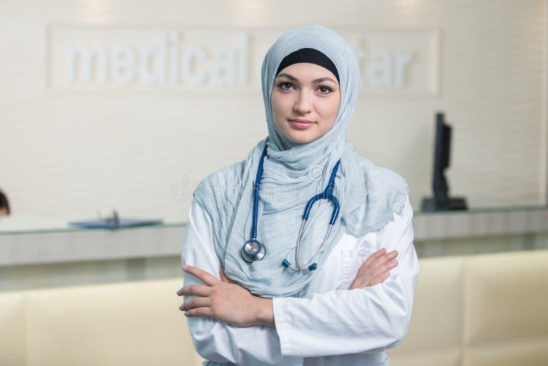 Close-upportret van vriendschappelijke, glimlachende zekere moslim vrouwelijke arts stock afbeeldingen