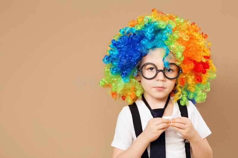 Close-upportret van Weinig jongen in clownpruik en oogglazen stock foto's