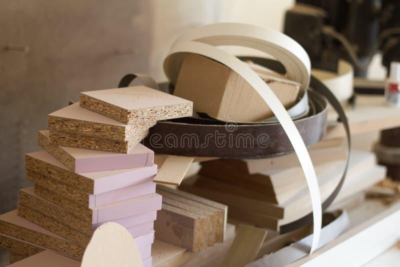 Close-upresten van spaanplaat en broodjes van de witte en bruine rand en de melanine van pvc voor de vervaardiging van meubilair  royalty-vrije stock afbeeldingen