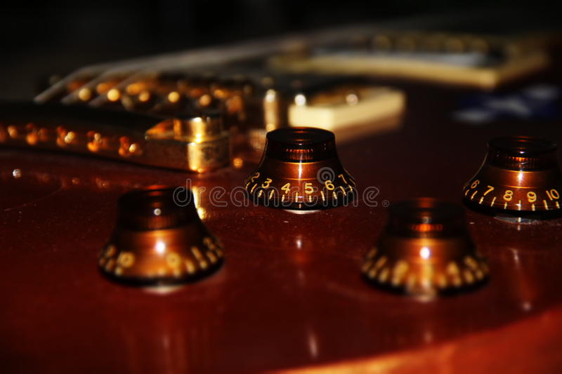 Close-ups of an electric guitar. Headstock: machine heads truss rod cover string guide nut Neck: fretboard inlay fret markers frets neck joint. Body neck pickup stock photos