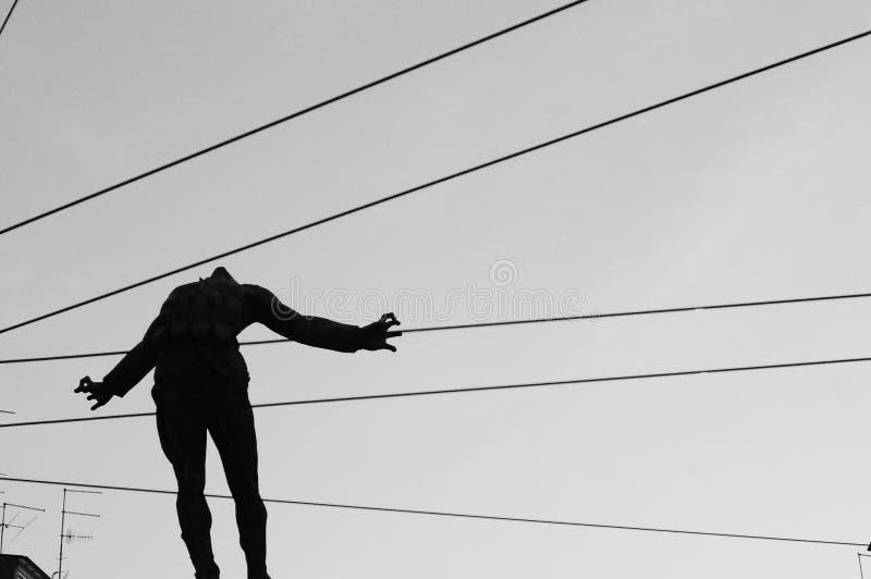 Close-upschot van een silhouet van een persoon in de lucht met kabels die achter het lichaam gaan stock foto's