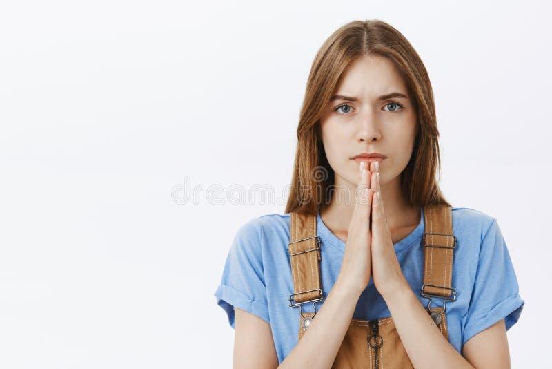 Close-upschot van ernstig-kijkt aspirant bepaalde leuke jonge vrouw met bevindende betrokken de holdingshanden van het kastanjeha stock afbeeldingen