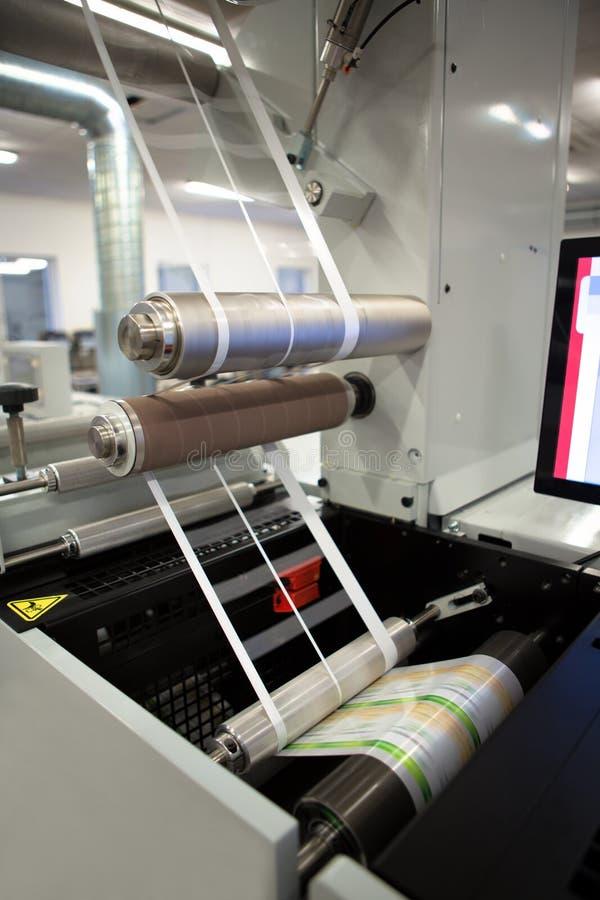 Close-upschot van etiketten die op de machine van de flexodruk vervaardigen Fotodetail van van de matrijsafval of versiering verw royalty-vrije stock afbeelding