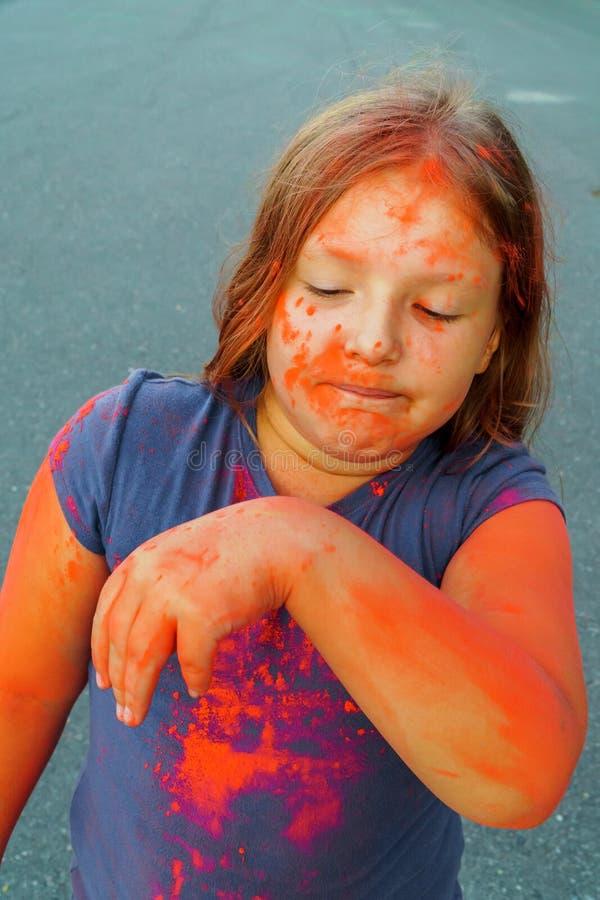 Close-upschot van jong kind dat met kleuren droge verf bij Holi-Festival wordt behandeld stock afbeelding
