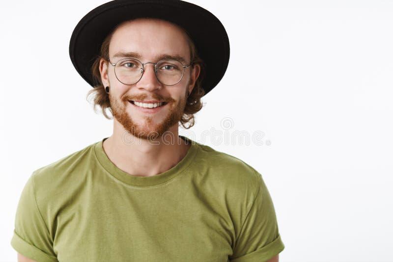 Close-upschot van knappe gelukkige jonge gebaarde hipsterkerel met doordrongen neus en baard in hoed en glazen het glimlachen stock foto