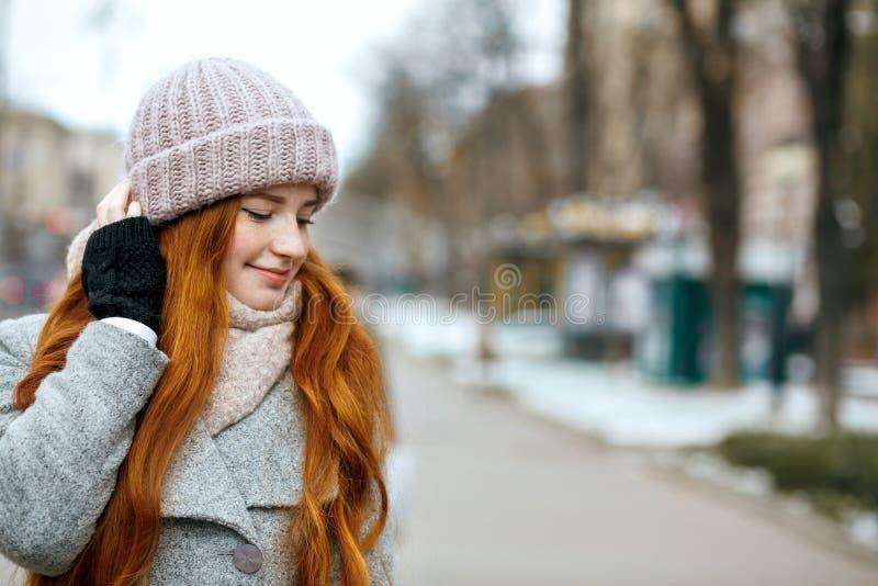 Close-upschot van mooie gembervrouw met lang haar die knitt dragen stock fotografie