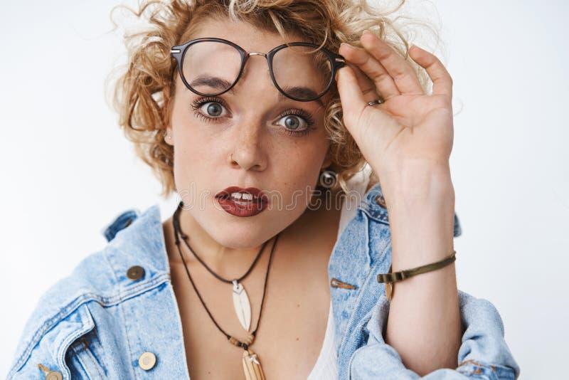 Close-upschot van verraste en geïmponeerde sprakeloze aantrekkelijke vrouw die ongelooflijke bevordering zien opstijgend glazen stock fotografie