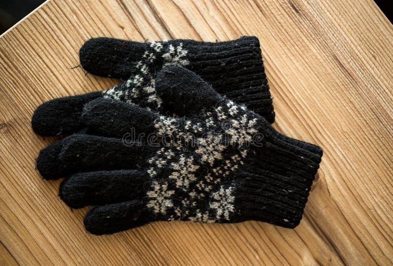 Close-upschot van zwarte gebreide handschoenen die op houten lijst liggen stock afbeeldingen