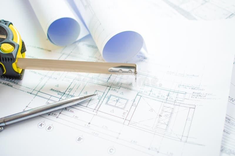 Close-upschoten van het bureau van de architect met blauwdruk architecturale projecten, pennen, die band en gebruiksklaar documen stock foto