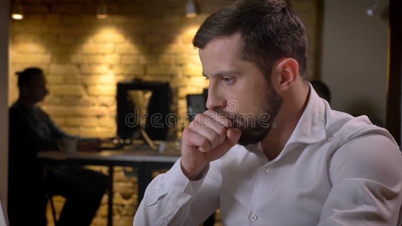 Close-upspruit van het volwassen Kaukasische zakenman typen op laptop die en ziek binnen in het bureau hoesten zijn stock afbeeldingen