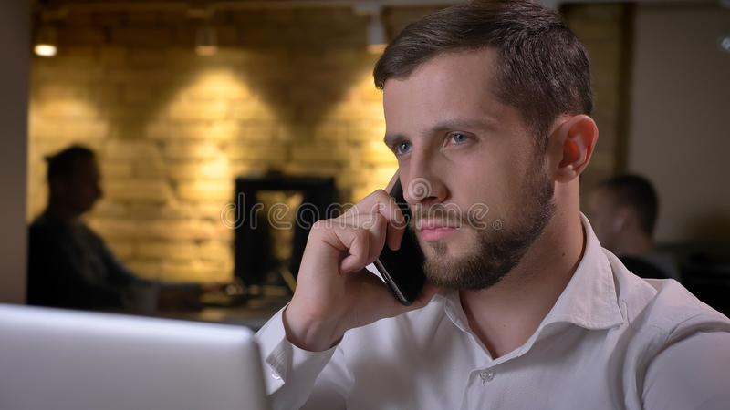 Close-upspruit van het volwassen Kaukasische zakenman typen op laptop en het hebben van formeel telefoongesprek binnen in het bur stock foto's