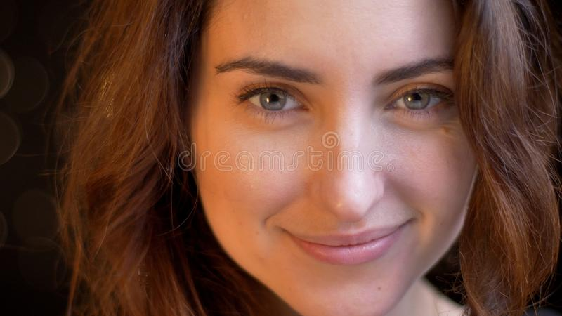Close-upspruit van jong aantrekkelijk Kaukasisch vrouwelijk gezicht die en recht camera met geïsoleerde achtergrond glimlachen be royalty-vrije stock foto's