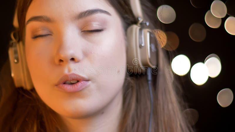 Close-upspruit van jong aantrekkelijk Kaukasisch wijfje die aan muziek in hoofdtelefoons luisteren en met bokehlichten zingen op stock foto