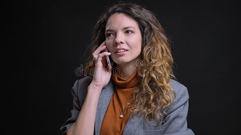 Close-upspruit van jong aantrekkelijk Kaukasisch wijfje die een toevallig gesprek op de telefoon voor de camera hebben met stock foto