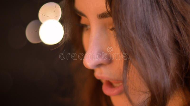 Close-upspruit van jong verleidelijk Kaukasisch wijfje die met charme met bokehlichten glimlachen op de achtergrond stock afbeelding