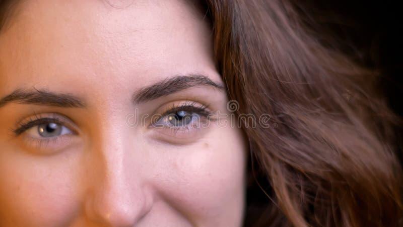 Close-upspruit van jong verleidelijk Kaukasisch wijfje die met ogen recht camera met het glimlachen gelaatsuitdrukking bekijken royalty-vrije stock afbeelding