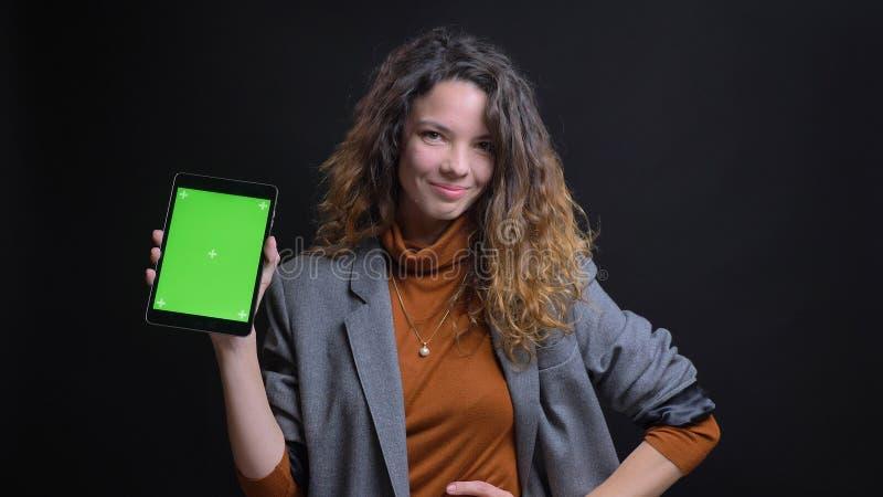 Close-upspruit van jong vrij Kaukasisch wijfje gebruikend de tablet en tonend het groene scherm aan camera met achtergrond stock afbeeldingen