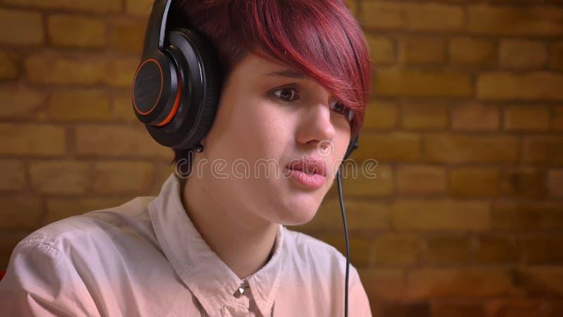 Close-upspruit van jong vrij tienerwijfje hipster videoblogger in hoofdtelefoons levend stromen terwijl het spelen van videospell stock foto's