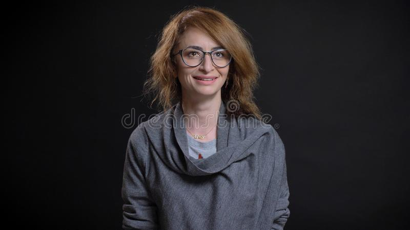 Close-upspruit van midden oud gelezen haired Kaukasisch wijfje die in glazen cheerfully terwijl het kijken vooruit met glimlachen royalty-vrije stock fotografie
