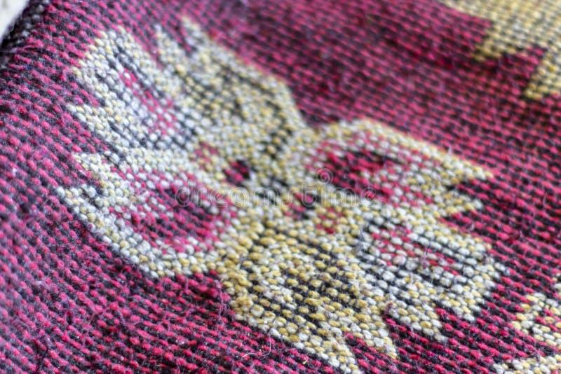 Close-upspruit van textuur van het detail de kleurrijke rode en gele tapijt met oosterse patronen stock afbeelding
