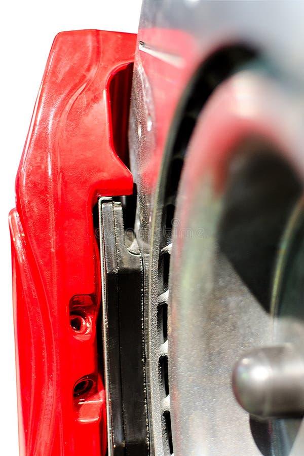 Close-upstootkussens op de rem van de schijfauto in rode beugel stock foto