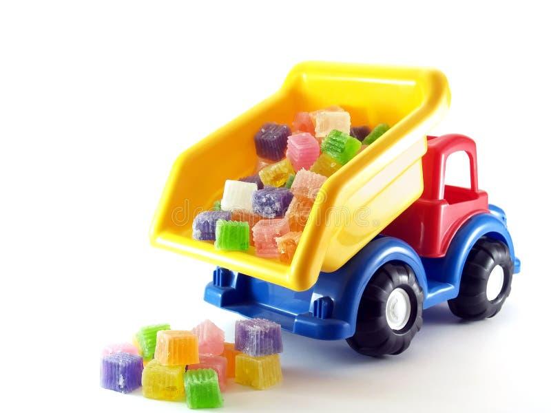 Close-upstuk speelgoed stortplaatsvrachtwagen die kleurrijk geleisuikergoed op witte achtergrond gieten stock afbeelding