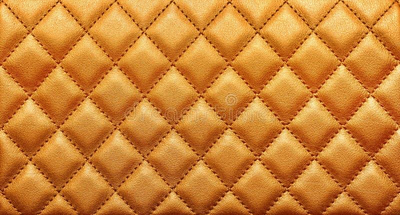 Close-uptextuur van echt leer met het ruitvormige stikken Rijke gouden kleur stock fotografie