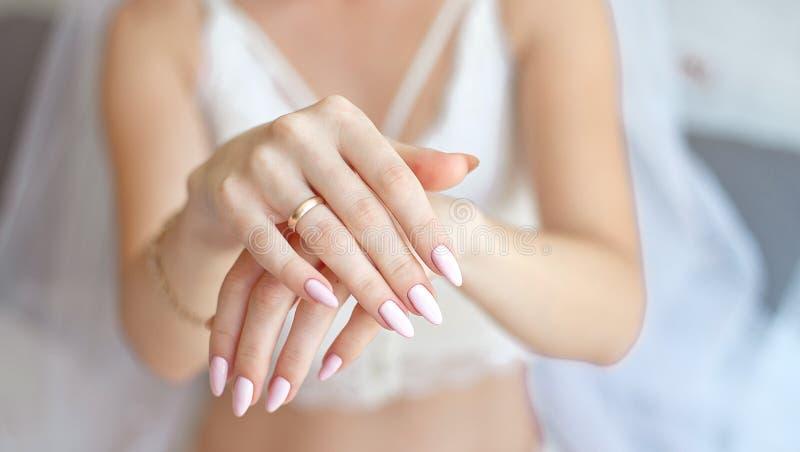 Close-upvrouw die haar handen met mooie manicure tonen De handen van de bruid met een aardige manicure stock afbeeldingen