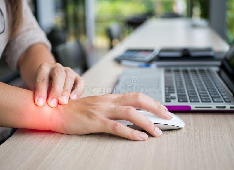 Close-upvrouw die haar polspijn van het gebruiken van computer houden stock afbeelding