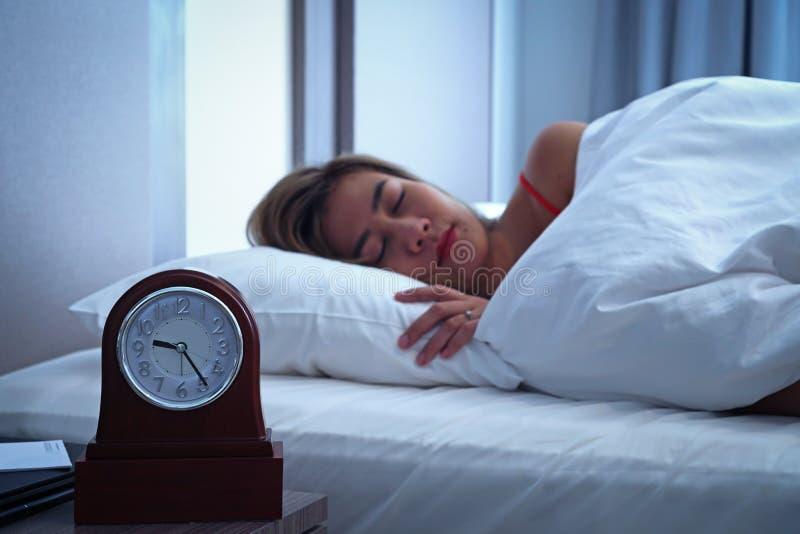 Close-upwekker die een goede nacht met achtergrond gelukkige vrouwenslaap hebben in bed royalty-vrije stock afbeeldingen