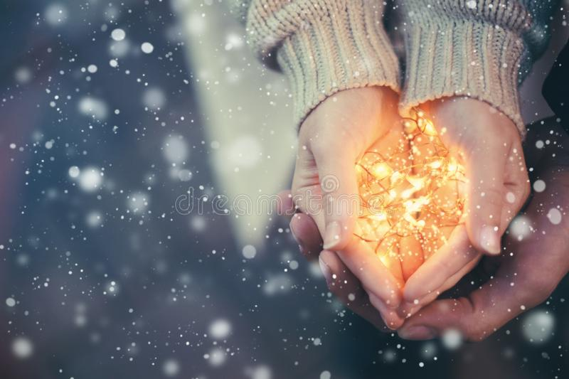 Close view of a couple holding warm Christmas lights. Snow falling vintage toning royalty free stock photography