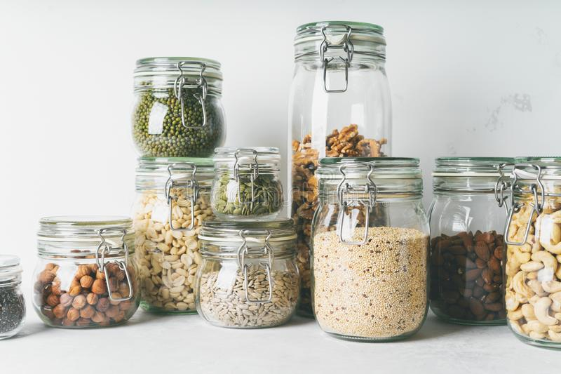 Glass jars with Superfoods nuts and cereals stacked on top of each other stock photo