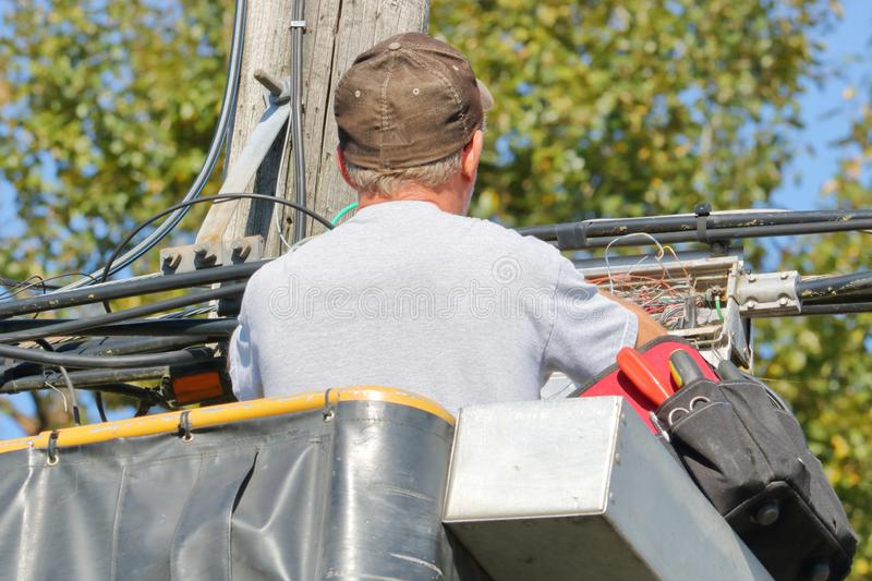 Close View of High Speed Internet Installer. Close, detailed view of a professional installer standing in a bucket or lift hooking up high speed internet for the royalty free stock images