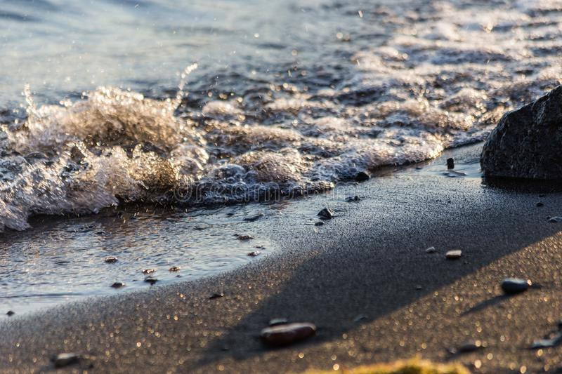 A close view of a lake shore, with details of sands, big and lit royalty free stock photo