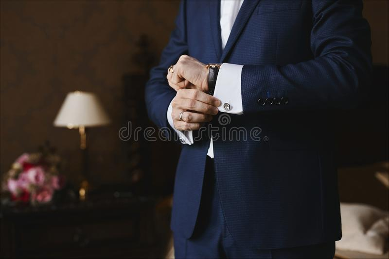 Close view of the luxury watches on the hand of a handsome businessman in a tuxedo and in a shirt with cufflinks.  royalty free stock photography